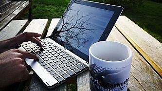 Laptop computer and coffee on outdoor table