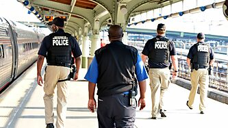 Homeland security agents in vests patrol a train station