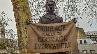 "Bronze statue of a woman holding a sign that says ""Courage calls to Courage everywhere"""