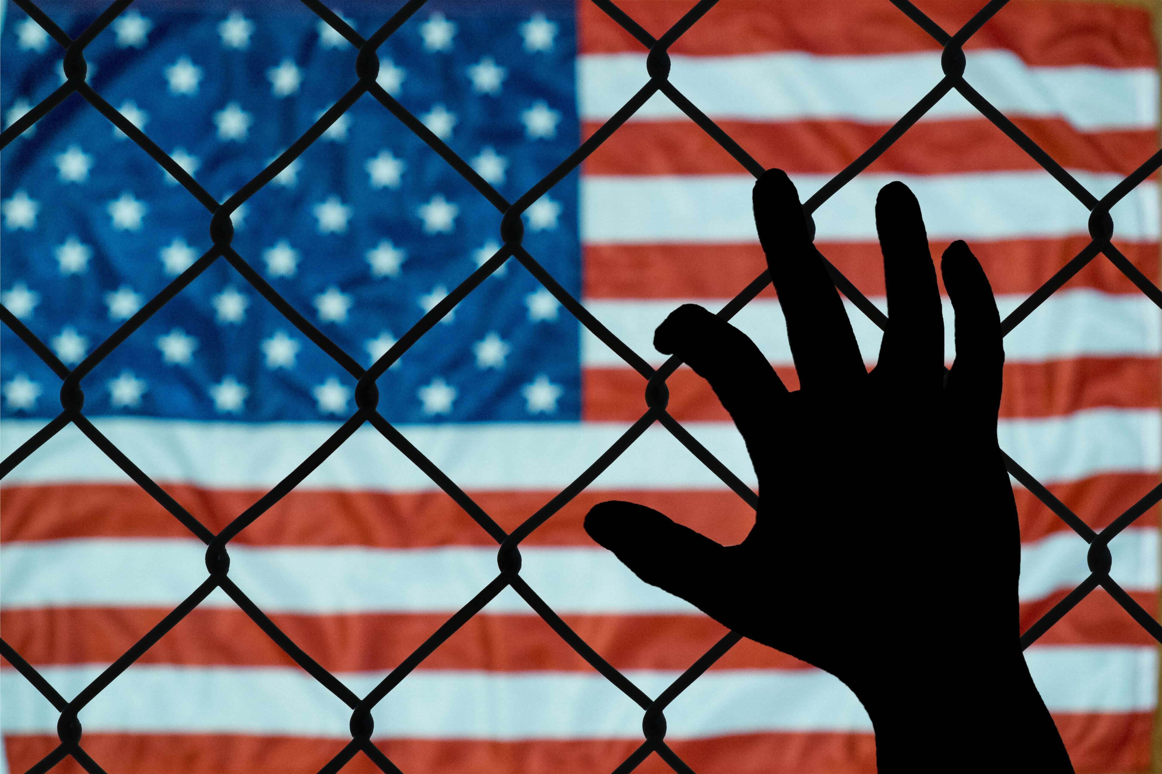 Hand holding a fence with American flag in the background