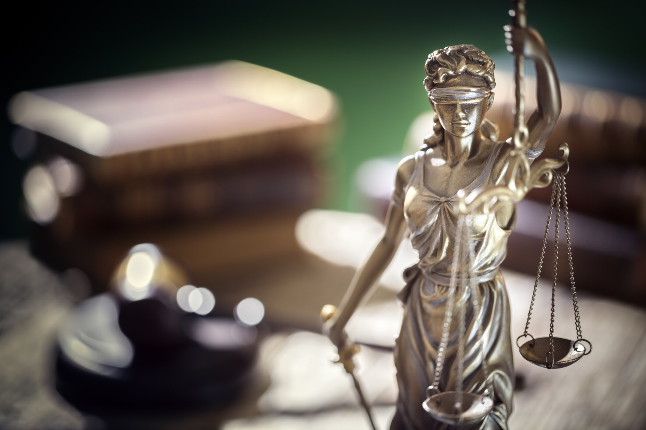 Lady justice with a gavel and books on a desk in the background