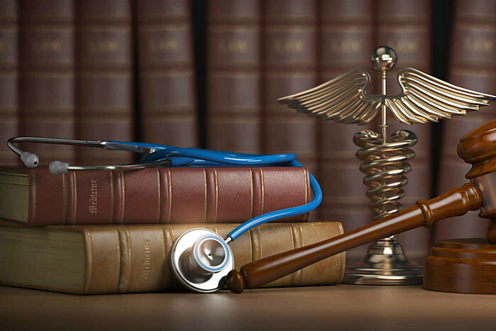 Stethoscope and Caduceus statue next to books of law and a gavel