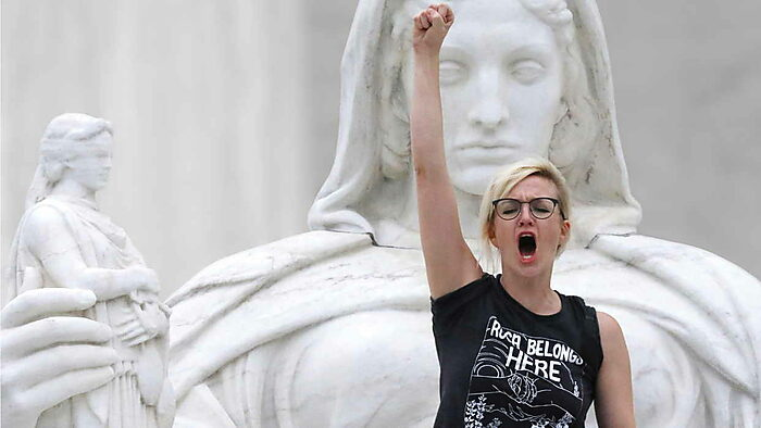 Woman with raised fist before a statue