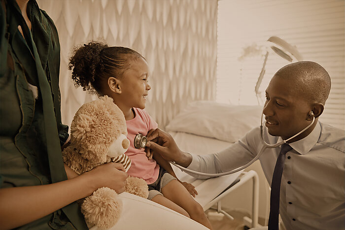 Black doctor places stethoscope on a smiling black child