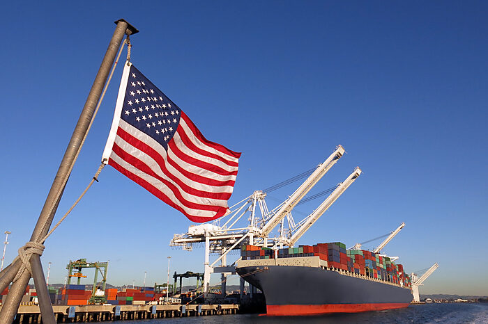 An American flag flies above a port where a container ship is unloading