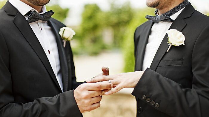 Two men in tuxedos putting rings on each other's fingers